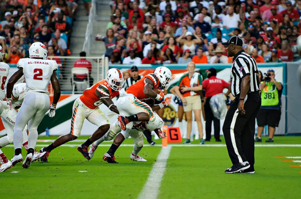 Hurricanes RB, Mark Walton, leaps over a defender for the endzone