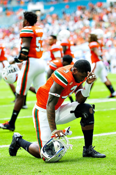 Hurricanes WR, Stacy Coley, says a prayer prior to the game