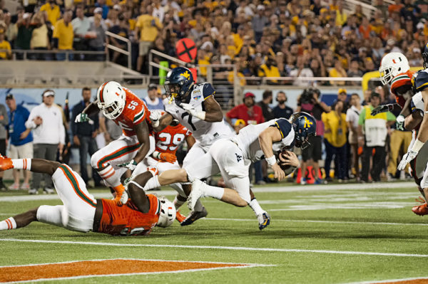 Miami Hurricanes DL, Chad Thomas, wraps up Sklyer Howard from West Virginia