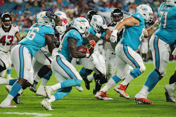 Dolphins RB, #34 Senorise Perry, tries to find a hole to run through