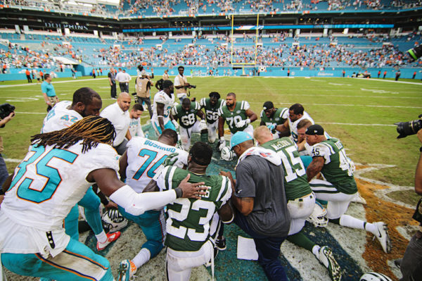 Players say a prayer at the 50 yard line
