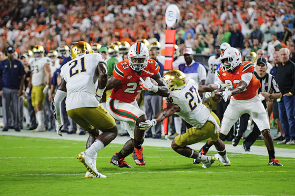 Hurricanes TE Chris Herndon (23) tries to run between two would be tacklers