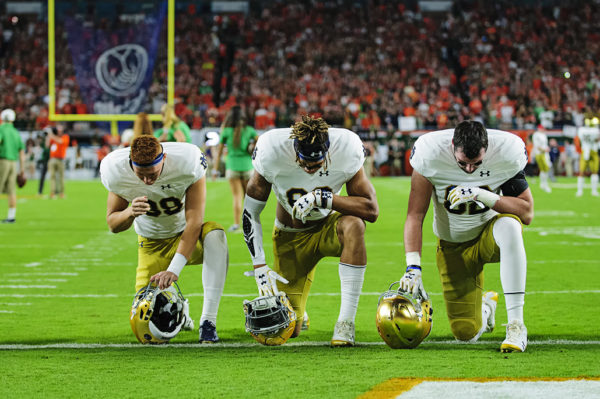 Notre Dame players take a knee in prayer before the game