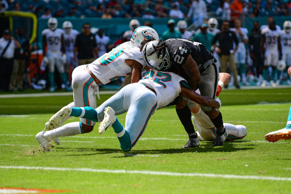 Miami Dolphins defensive back T.J. McDonald (22) and Miami Dolphins defensive back Minkah Fitzpatrick (29) try to tackle Oakland Raiders running back Marshawn Lynch (24)