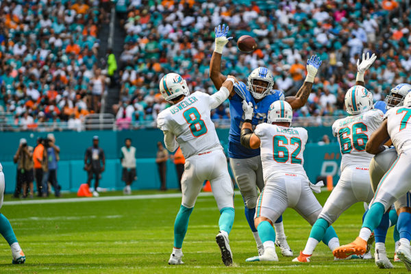 Miami Dolphins quarterback Brock Osweiler (8) throws a pass between the hands of Detroit Lions defensive end Da'Shawn Hand (93)