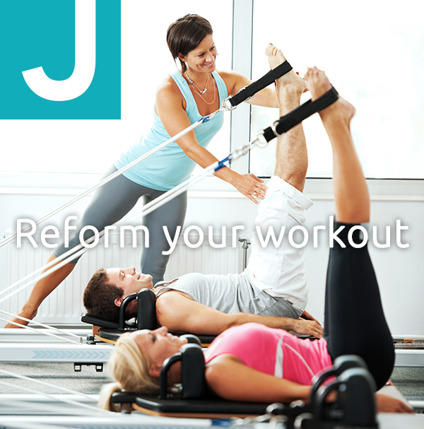Two people exercising on a Pilates machine with the help of an instructor.