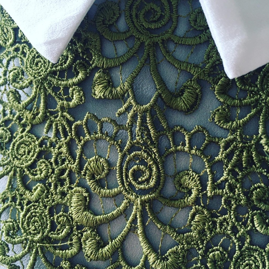 Some green machine embroidered lace under a white shirt collar