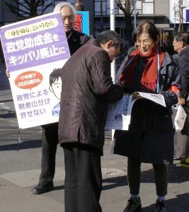 呼びかけに応えて署名する男性=19日、東京・大塚駅前