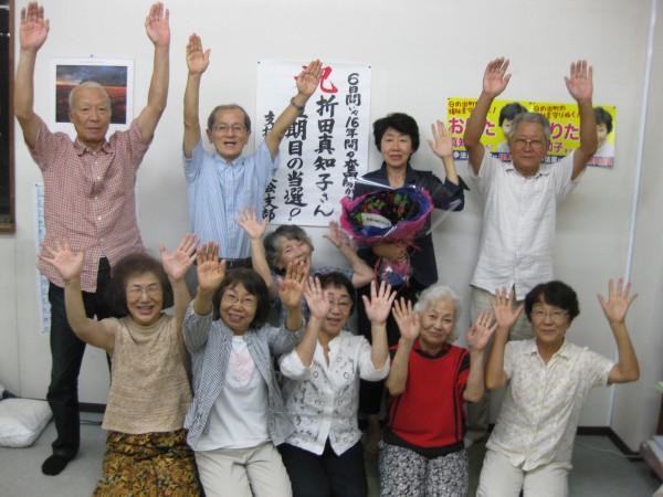 支援者と当選を喜び合う、おりた氏(後列右から2人目)=23日、東京都日の出町