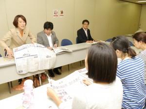「しんぶん赤旗」特別号を広げ国民連合政府の提案を説明する田村参院議員(左端)とママの会出席者(手前)=10月31日、東京都墨田区