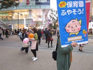 新宿駅東南口でプラスターを掲げ「赤旗」号外を配る「日本共産党を応援する東京保育の会」の人たち