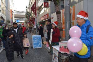 サンタの帽子をかぶって「子どもたちに平和を送ろう」と訴える人たち=24日、世田谷区