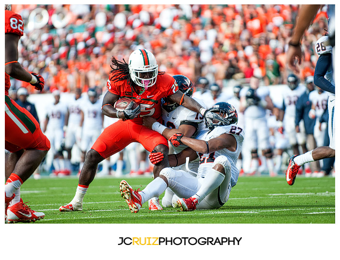 Hurricanes RB #25, Dallas Crawford, tries to elude tacklers from Virginia