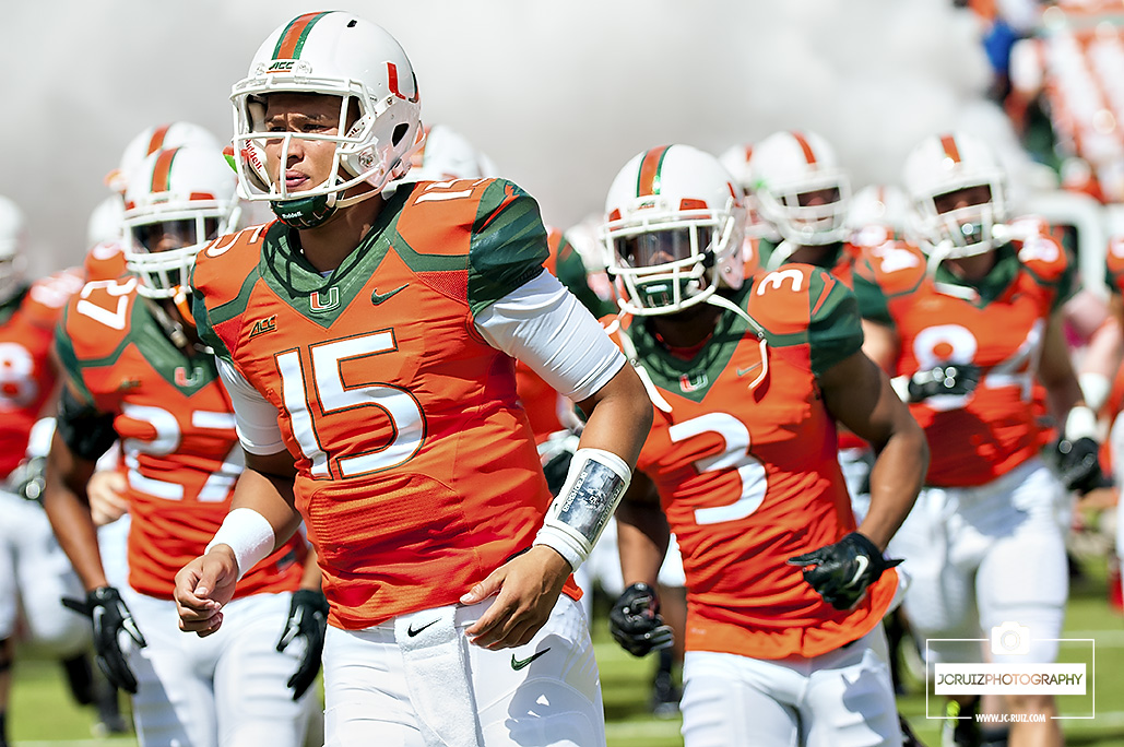 Miami QB Brad Kaaya runs out of the smoke before the game