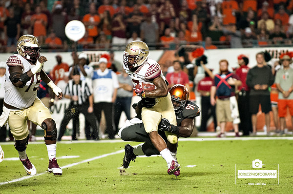 Miami Hurricanes DL # 91, Olsen Pierre, attempts to tackle Florida State RB #7, Mario Pender
