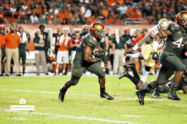 Miami RB #8 Duke Johnson attempts to rush against the Florida State defense