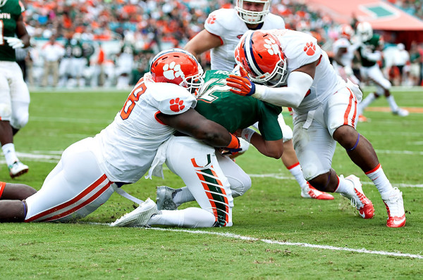 Miami Hurricanes QB #12, Malik Rosier, gets sandwiched by two Clemson defenders