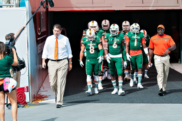 Miami Headcoach, Al Golden, leads his team out before the game