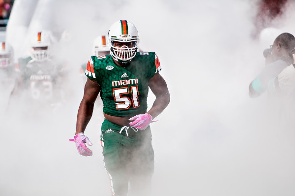 Miami Hurricanes LB #51, Juwon Young, runs through the smoke
