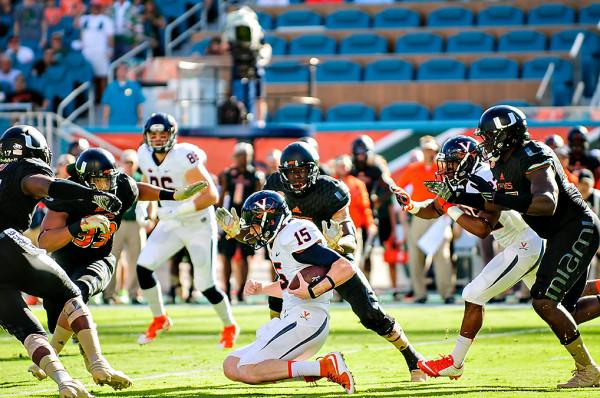 Virginia QB Matt Johns slides to avoid a tackle