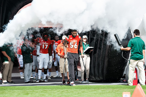 Injured linebacker, Raphael Kirby, walks through the smoke