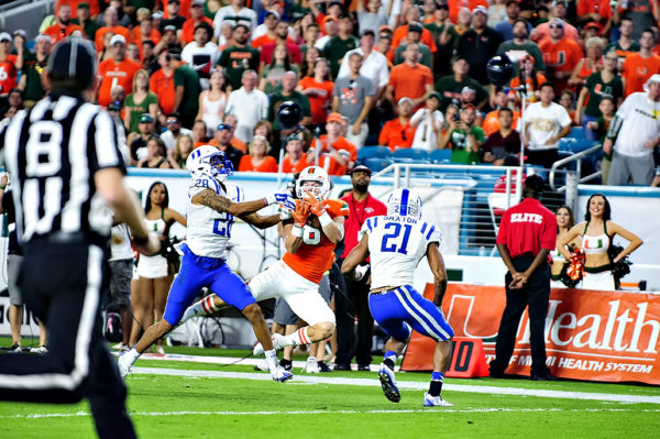Braxton Berrios makes a catch between two defenders