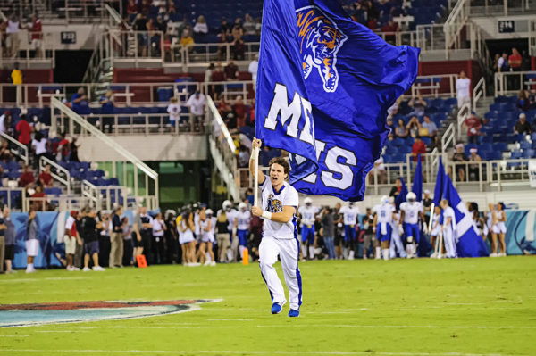 A member of the Memphis cheer squad leads the team onto the field