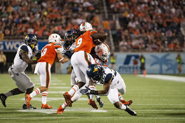 Malcom Lewis, Hurricanes WR, tries to leap past a defender from West Virginia