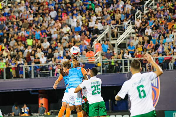 A Miami FC player heads the ball