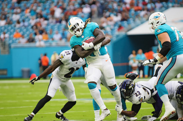 Dolphins RB #23, Jay Ajayi, tries to break tackles