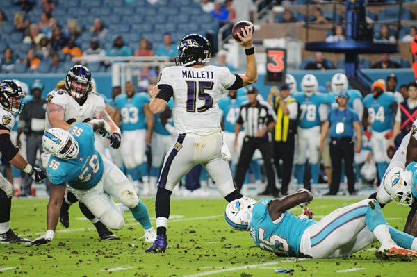 Ryan Mallett, Ravens QB #15, throws the ball under pressure from the Dolphins defense