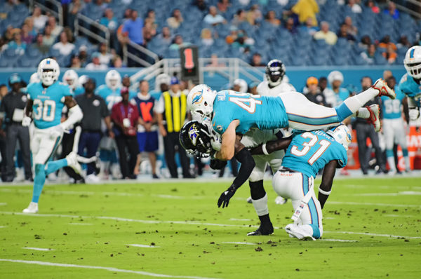 Dolphins LB #45, Mike Hull, jumps on the back of #7, Javorius Allen