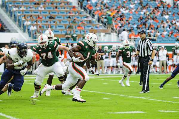 Hurricanes RB, Mark Walton, finds an opening to run through