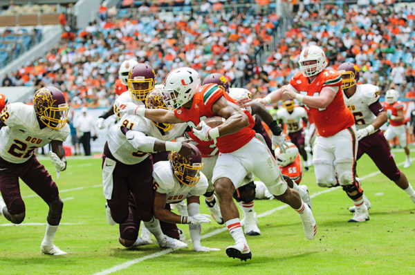 Hurricanes RB, Travis Homer extends a stiff arm to a defender