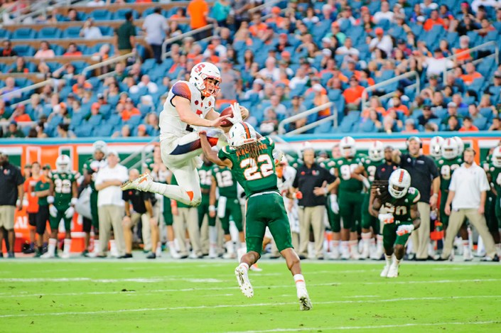 Eric Dungey (2) tries to leap over Sheldrick Redwine (22)