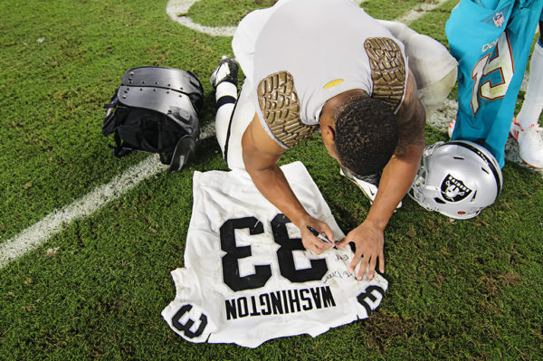 DeAndre Washington (33) writes a message on his jersey