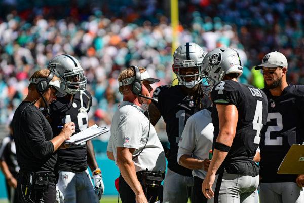 Coach Jon Gruden talks to Oakland Raiders quarterback Derek Carr (4) during a timeout