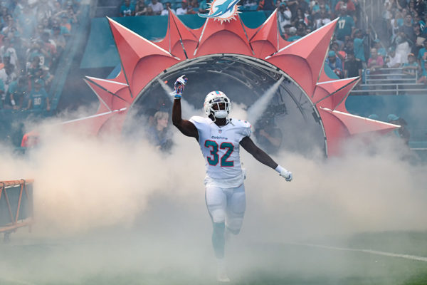 Miami Dolphins running back Kenyan Drake (32) emerges through the smoke