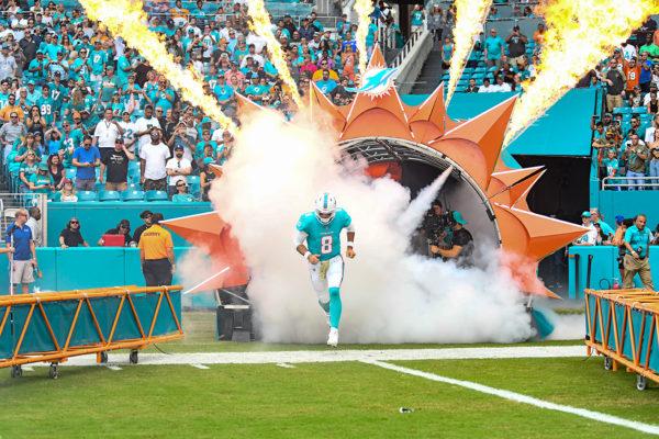 Miami Dolphins quarterback Brock Osweiler (8) runs through the smoke