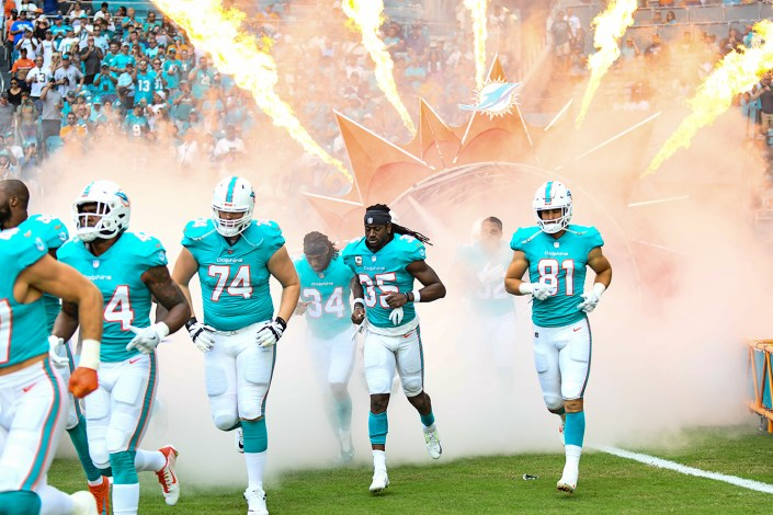 Miami Dolphins players run onto the field