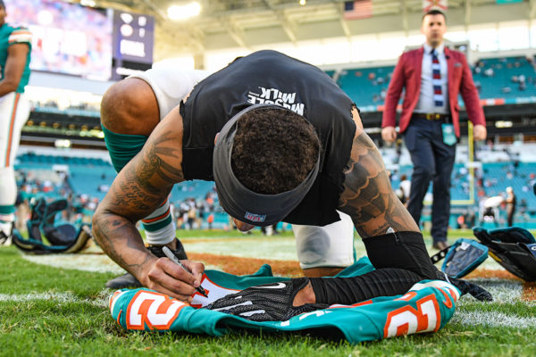 Miami Dolphins cornerback Torry McTyer (24) signs his jersey