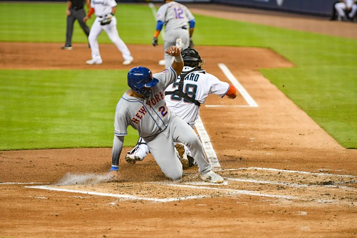 New York Mets first baseman Dominic Smith #22 slides across home plate
