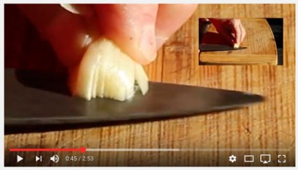 Image of a section of an instructional movie about cutting garlic