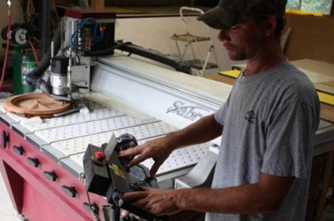 JDMDesigns worker operates the CNC machine