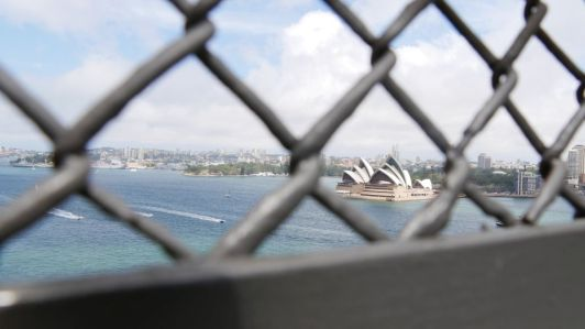 Sydney Opera House gefotografeerd door het hek op de Harbour Bridge