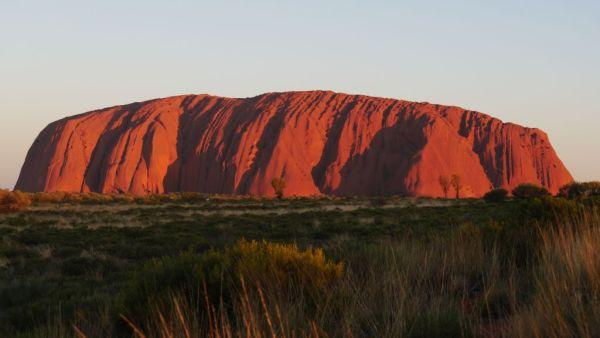 De grote rode rots in Uluru, Australië die een rode gloed afgeeft tijdens de zonsondergang