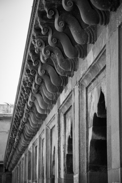 The row of scrolls supports the chhajja, which is the hindi name for the eaves that project out over the arches.