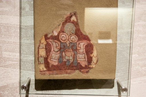 A very stylized representation of a butterfly, with a hand in the center. This figure has 'goggle' eyes, like those on the depictions of Tlaloc on the Temple of Quetzalcaoatl.