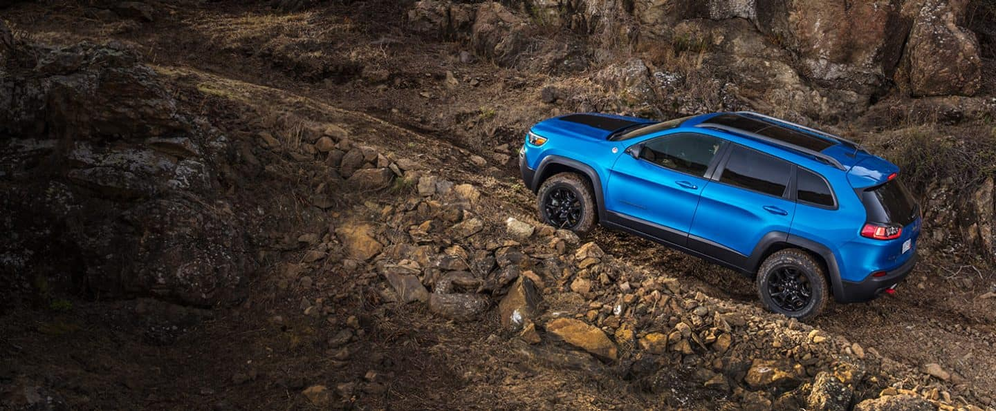 hight resolution of jeep cherokee trailhawk crawls up a rocky incline