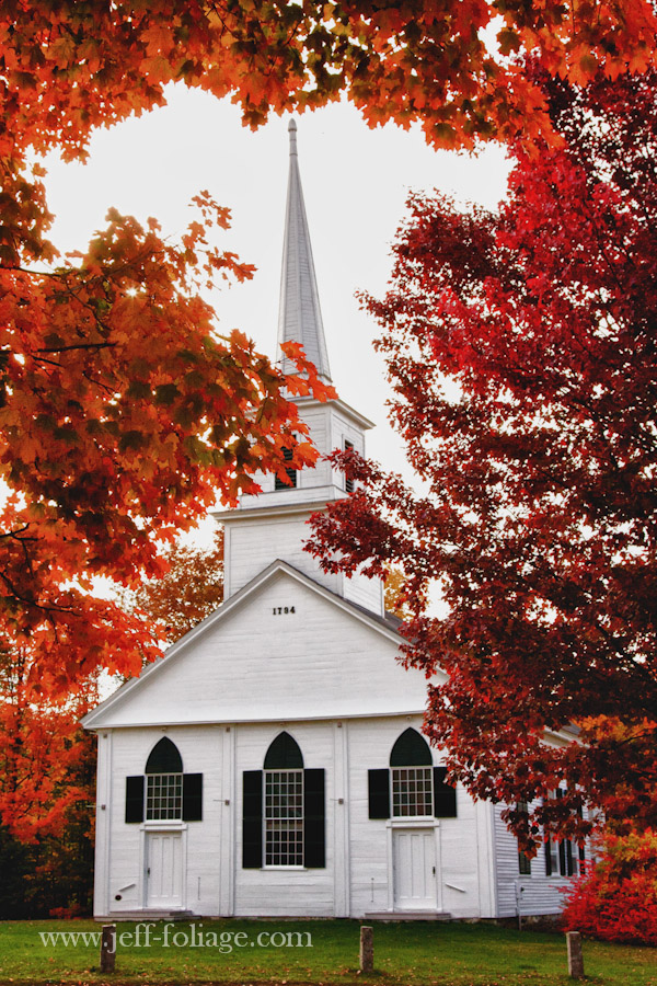 white church with tall steeple in New Salem with red and orange fall foliage